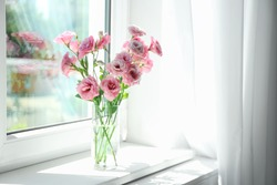Glass vase with beautiful flowers on window sill in room, space for text