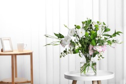 Glass vase with bouquet of beautiful flowers on table in room. Space for text