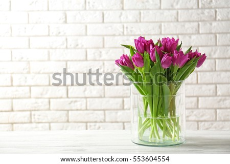 Glass vase with bouquet of beautiful tulips on brick wall background #553604554