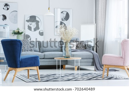 Stock Photo Glass vase with flowers on coffee table in stylish living room with designer armchairs and grey sofa