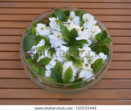 glass vase with gardenia flowers on wooden table