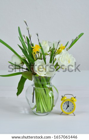 Glass vaza with a bouquet of spring flowers and yellow alarm clock.Bunch of pussy willow branches with catkins and white roses.Spring card for Mother's Day, Women's Day. copy space.