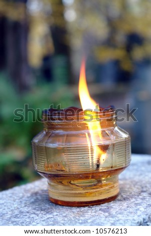 Glass votive candle lit on tombstone
