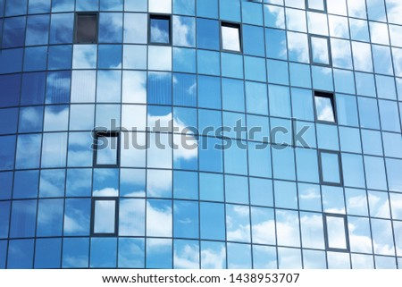 Glass wall facade with cloud sky reflection. Modern urban architecture background. Skyscraper business center, bank or hotel in city downtown. Glassy megalopolis exterior #1438953707
