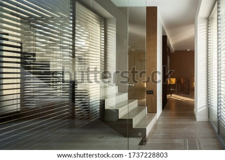 Glass wall in home corridor with modern stairs and big window