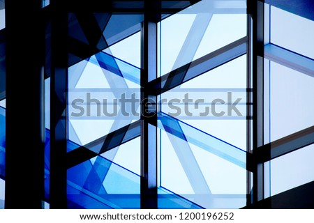 Glass wall with aluminum or steel framework. Structural glazing. Reworked close-up photo of office building fragment in shadows against clear blue sky. Abstract modern architecture background. #1200196252