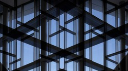 Glass wall with metal framework. Reworked photo of office building exterior or interior fragment. Windows as abstract modern architecture background with geometric structure with blue sky.