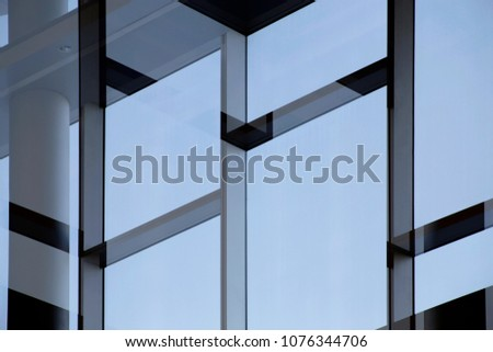 Glass wall with metal framework. Structural glazing. Fragment of office building fragment against clear blue sky. Abstract modern architecture with empty frames for text placement. #1076344706