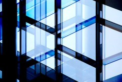 Glass wall with steel or aluminum framework. Structural glazing. Reworked close-up photo of office building fragment in shadows against clear blue sky. Abstract modern architecture background.
