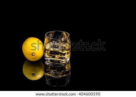 Glass whiskey with ice and lemon on black background #404600590