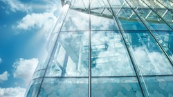 Glass windows of contemporary business building with clouds reflection close-up. Modern architecture with blue cloudy sky and sun rays.