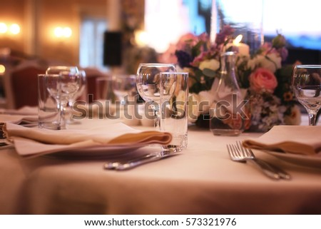 Glass wine glasses on the table served for the reception in the restaurant #573321976
