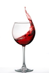 Glass with a splash of red wine isolated on white background