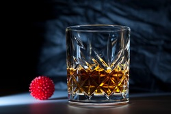 Glass with alcohol. Concept - protection against a pandemic coronavirus (COVID-19)  with strong alcoholic beverages. Whiskey, brandy, brandy, tequila, vodka can be used as disinfectant liquids.