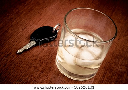 Glass with alcoholic beverage and car key on the wooden table