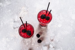 Glass with Alcoholic Blackberry Lemonade Beverage. Cool Refreshing Blueberry Cocktail and Ice Cubes in Goblet. Homemade Juicy Vitamin Drink with Tubules on Light Background Top View