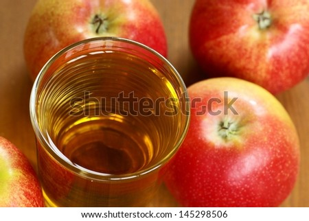 Glass with apple juice and apples.