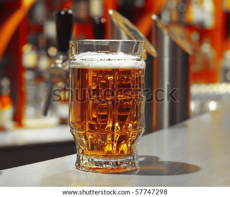 Glass with beer on table in a pub