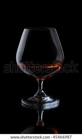 Glass with cognac on a black background.