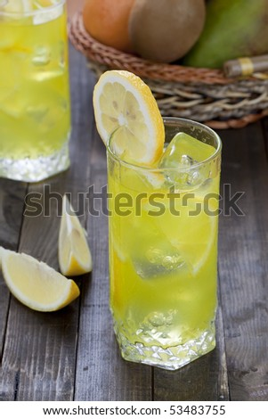 Glass with cold lemon beverage on wooden table top