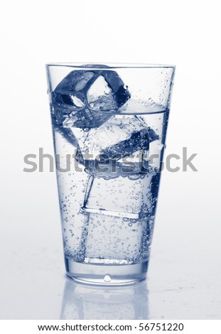 glass with cold mineral water, bubbles and ice
