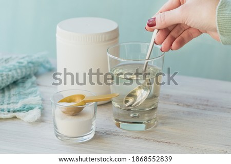 Glass with collagen dissolved in water and collagen protein powder on white wooden table. Woman's hand holds a spoon. Healthy lifestyle concept. Photo stock ©