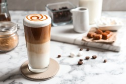Glass with delicious caramel latte on table