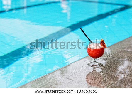 glass with drink costs on a pool side