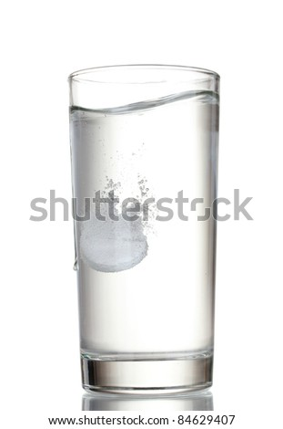 Glass with efervescent tablet in water isolated on white