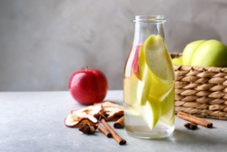 Glass with fresh apple water and cinnamon sticks on light table