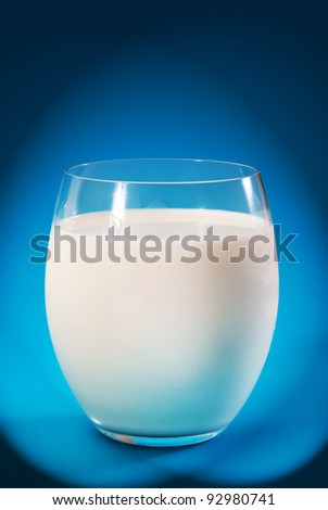glass with fresh milk on blue background
