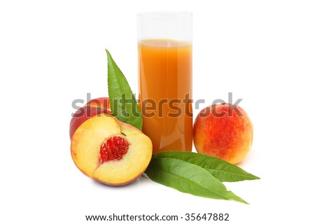 Glass with freshly made peach juice and leaves on a white background