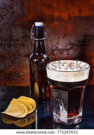 Glass with freshly poured dark beer, beer bottle near scattered chips on a black mirror surface. Food and beverages concept #775287652