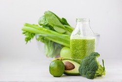 glass with green healthy smoothie, nutritious breakfast, vegetarian food, raw vegetables in the morning, broccoli, avocado, celery, salad, kiwi apple, lime. healthy eating for the whole family, diet