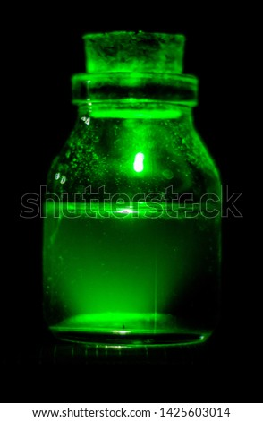 Glass with green liquid, glass bottle with green liquid, green liquid in glass bottle. #1425603014