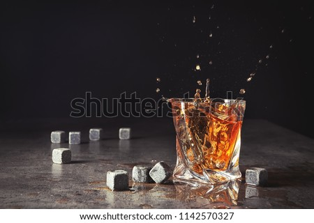 Glass with liquor splash and whiskey stones on table #1142570327