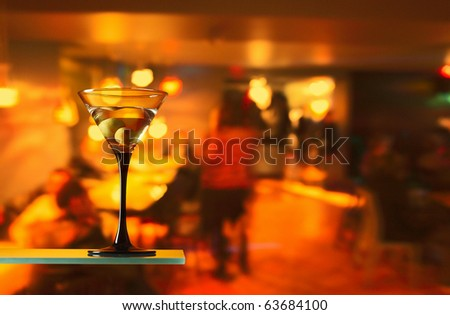 glass with martini and green olives.