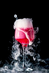 Glass with pink drink and dry ice smoke, bubbles, background