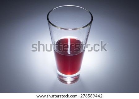 Glass with red liquid, red juice