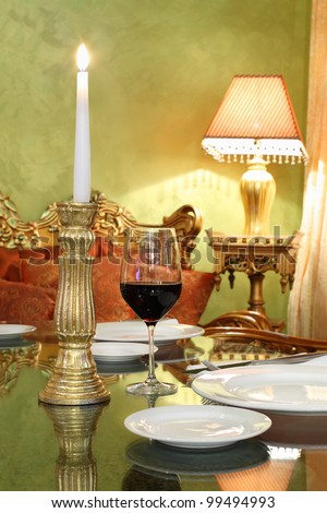 glass with red wine and gold candlestick with candle at table in cozy restaurant
