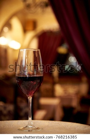 Glass with red wine on a background of a blurry restaurant #768216385