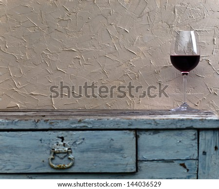 glass with red wine on a old table