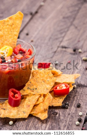 Glass with Salsa Sauce and Nachos on wooden background