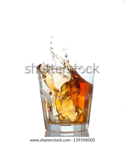Glass with splashing whisky drink. Isolated on a white background #139508000