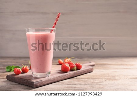 Glass with tasty strawberry smoothie on wooden table