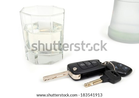 Glass with vodka and car keys. white background