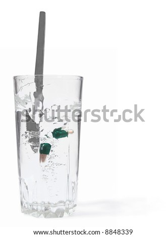 Glass with water and pills.