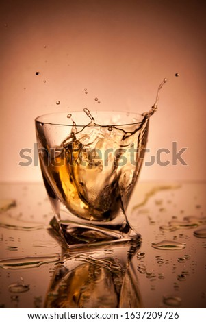 Glass with whiskey and spray on an lush lava background. Alcoholic drink in a glass. Ice falls into a bowl with liquid. Steel glass for a strong beverage. Splash of drops and spray from a glass.