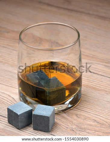 Glass with whiskey and whiskey stones on wooden background #1554030890