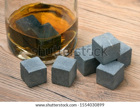 Glass with whiskey and whiskey stones on wooden background #1554030899